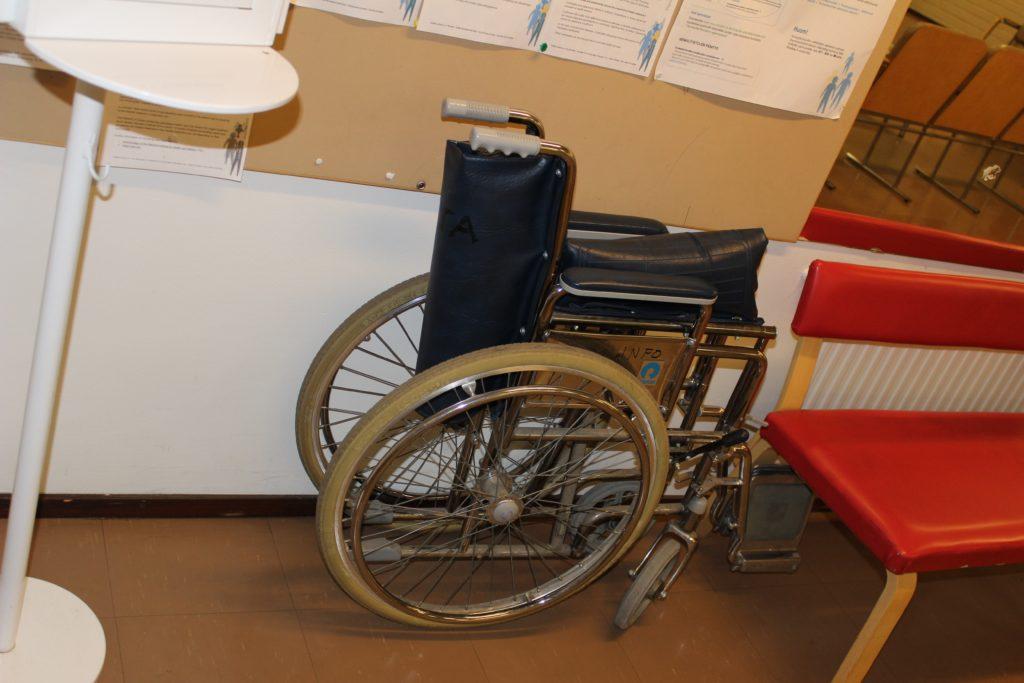 Terveyskeskuksen seinää vasten oleva pyörätuoli.