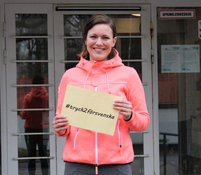 """På fotot visas en person som håller en lapp där det står """"#tryck2försvenska""""."""