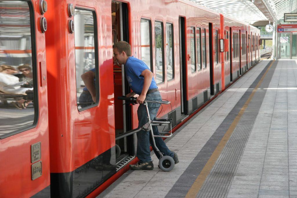 Person med rullator stiger ombord på metrotåget i Helsingfors.