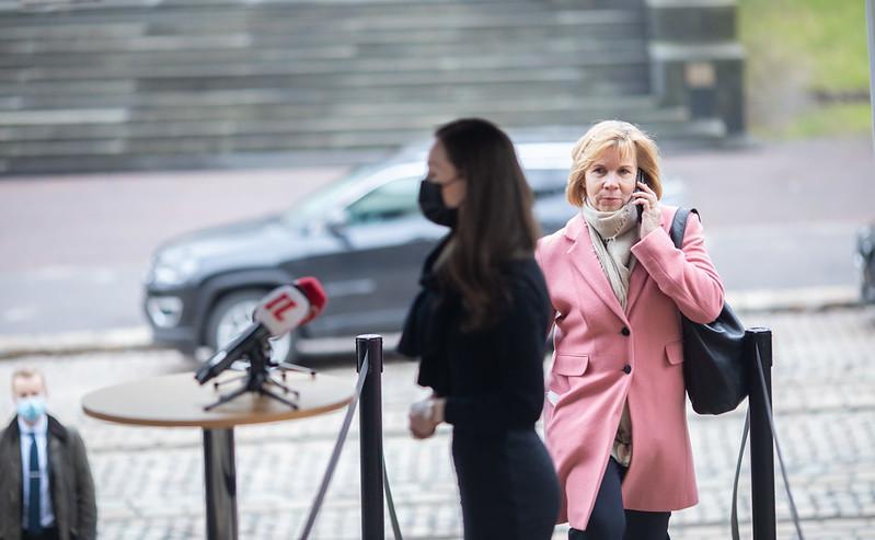 Justitieminister Anna-Maja Henriksson på väg mot förhandlingsbordet medan statsminister Sanna Marin svarar på pressens frågor.