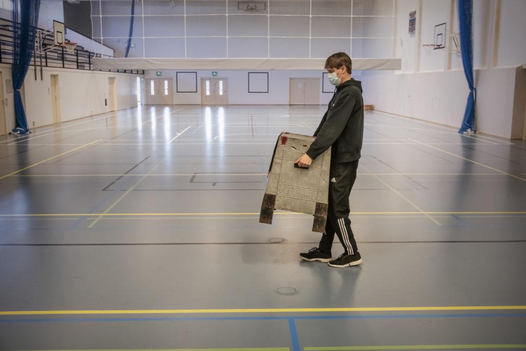 Valförberedelser i Lillkyro i Vasa. Den över hundra år gamla valurnan som vaktmästaren Mikko Taittonen ställer fram används i vallokalen i Savilahden yhtenäiskoulu.